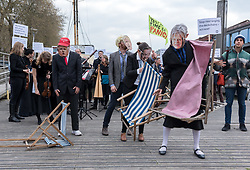 © Licensed to London News Pictures. 12/04/2019. Bristol, UK. Actors with facemasks of Nigel Farage, Theresa May, Boris Johnson, Michael Gove, Donald Trump and Vladimir Putin for an Extinction Rebellion Performance Action coordinated by the EarthQuakes and Evergreens XR affinity groups together with the Insight Ensemble at Cascade Steps in Bristol city centre, with a painting of the sinking of The Titanic, a flash mob of musicians playing 1912 music as the Titanic sinks whilst actors dressed as national and international politicians re-arrange the deckchairs, as a metaphor for the imminent climate crisis. The idea was originally thought of by Jo Flanagan after she heard that her daughter was expecting her first child. It is hoped that this Extinction Rebellion performance action will be repeated in London during the Extinction Rebellion week of action beginning 15th April. Photo credit: Simon Chapman/LNP