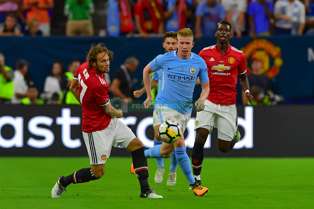 Manchester City midfielder Kevin De Bruyne (17) and Manchester United midfielder Daley Blind (17) race for possession during the International Champions Cup match between Manchester United and Manchester City at NRG Stadium in Houston, Texas