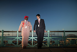 © Licensed to London News Pictures . 27/09/2015 . Brighton , UK . Labour Party activists JOSEPH AFRANE ( 51 from Battersea in London ) and JOE COLEMAN (21 from Islington in London ) talking in the morning sun outside the Labour Party Conference on Brighton seafront . The 2015 Labour Party Conference . Photo credit : Joel Goodman/LNP