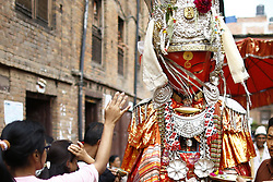 August 19, 2017 - Bhaktapur, Nepal - Devotees offer prayers to a person concealed inside the idol of Deity Dipankar Buddha parading around the ancient city to receive prayers offered by devotees during Pancha Dan festival in Bhaktapur, Nepal on Saturday, August 19, 2017. The major highlights of the festival are giving away five elements also known as five summer gifts including wheat grains, rice grains, salt, money and fruit for prayers, wishing good health and prosperity. The Buddhists observe Pancha Dan by displacing gigantic antique statues of Deity Dipankar Buddha and devotees worshipping them across the city. (Credit Image: © Skanda Gautam via ZUMA Wire)
