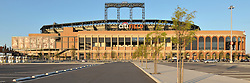 Panoramic view of Citi Field, Home of the Mets, Flushing, Queens, New York City. West elevation as a brilliant sun sets behind the camera. No game day, empty parking lot.