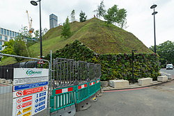 """© Licensed to London News Pictures. 13/08/2021. LONDON, UK.  Construction entrance at Marble Arch Mound.   Westminster City Council has announced that deputy leader, Melvyn Caplan, has resigned after the cost of the mound, initially reported as £2m, is now estimated at £6m. Commissioned by the council and designed by MVRDV architects, the 25m high artificial mound has been heavily criticised as being incomplete, lacking the advertised views, too expensive for a visit and """"being the worst landmark in London"""".  Currently free to visit during August, the mound is planned to reopen fully in September.  Photo credit: Stephen Chung/LNP"""