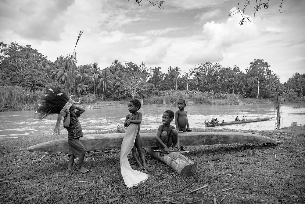 Children play in the village of Yar, located on the Keram River in East Sepik Province, Papua New Guinea. One boy has a headdress made of cassowary feathers. (June 23, 2019)