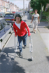 Girl with Cerebral Palsy using frame to walk along pavement,