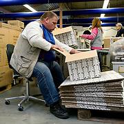Nederland Rotterdam 11 december 2007 .Werknemer van Roteb Impact vouwt dozen waar kerstpaketten in geplaatst zullen worden. Werknemers van Roteb Impact stellen kerstpakketten samen en pakken deze in aan de lopende band. Roteb Impact is een sociale werkplaats voor minder validen en geestelijk gehandicapten. ..Roteb heeft banen voor mensen die door psychische, lichamelijke of verstandelijke beperkingen alleen kunnen werken onder aangepaste omstandigheden. Rotterdammers met een handicap en op zoek naar een baan bij Roteb Ultimade, Roteb MultiGroen, Roteb Impact of andere Roteb-onderdelen dienen zich te melden bij het dichtstbijzijnde CWI...Roteb richt zich onder meer op werkgelegenheid, arbeidsintegratie en uitvoering van de Wet sociale werkvoorziening (Wsw). Roteb biedt werk aan mensen die met psychische, lichamelijke of verstandelijke beperkingen alleen kunnen werken onder aangepast omstandigheden. Daarnaast biedt Roteb leerwerkplaatsen voor andere doelgroepen met een afstand tot de arbeidsmarkt om ze meer kans te bieden op een reguliere baan..Roteb biedt in de 4 werkbedrijven, Impact, Montaz, Ultimade en MultiGroen aangepast werk. Daarnaast werken medewerkers individueel gedetacheerd of in een werkunit op locatie bij de klant. Als het nodig is begeleidt Roteb medewerkers die willen en kunnen uitstromen naar de reguliere arbeidsmarkt..Voor zover mogelijk sluit Roteb de mogelijkheden van arbeidsgehandicapten en de vragen op de reguliere arbeidsmarkt op elkaar aan. Daardoor vinden mensen met een lichamelijke, verstandelijke of psychische beperking werk dat bij hen past. We onderhouden intensieve contacten met verwijzende instellingen, belangenorganisaties en praktijkscholen. Onze werkbedrijven hebben veel zakelijke relaties in de markten en springen in op nieuwe mogelijkheden. Zij vernieuwen hun diensten en producten in samenspraak met hun partners..Roteb divisie multibedrijven is de nieuwe naam voor de werkzaamheden van Multibedrijven en Inderdaad..Multibedrijven is e