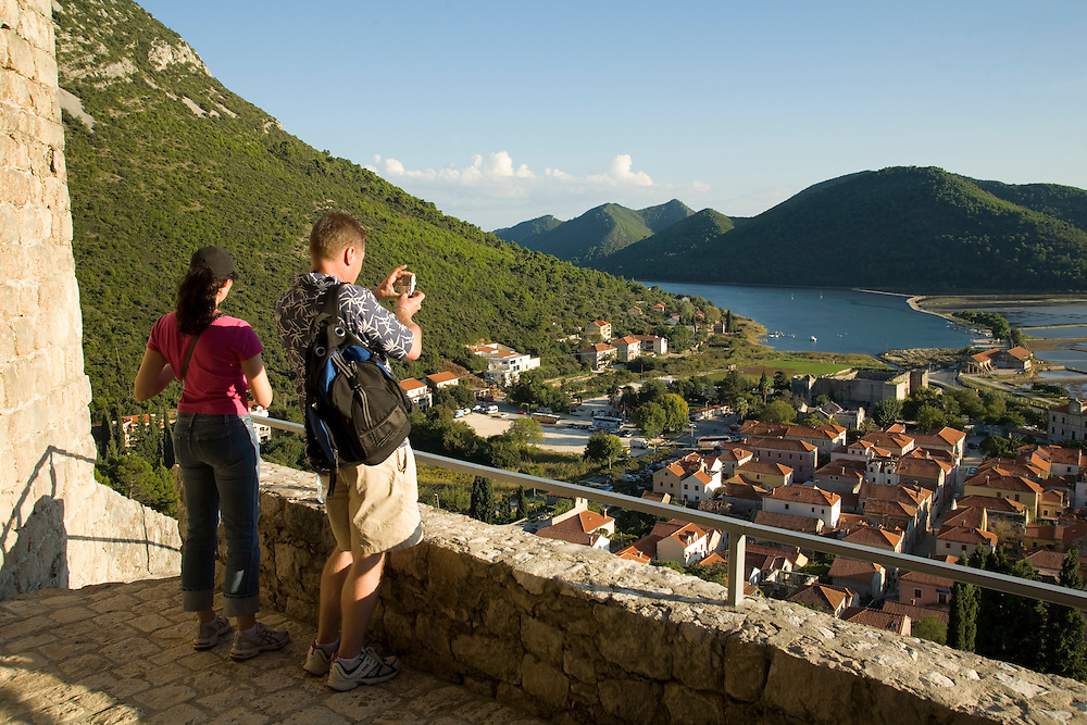 Europe, Croatia, Dalmatia, Mali Ston.  Man and woman photoghing at salt pans, lush hills and village of Mali Ston, from walls of 15th century fort.