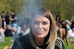 © Licensed to London News Pictures. 20/04/2019. London, UK. A woman smokes marijuana as thousands of revellers gather in London's Hyde Park as part of '4/20 Day', an unofficial International Weed Day, an event that takes place every year on 20 April for people to smoke cannabis without been detained. Attendees are calling on the Government to decriminalise Class B drug and raise awareness about the drug. Photo credit: Dinendra Haria/LNP