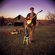 A man poses on a stool holding his banjo on a country farm.