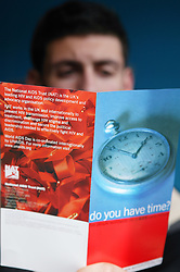 Young man reading a leaflet produced by the National Aids Trust NAT; model released for use in HIV and Aids,