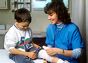 Nurse comforts young boy patient with injury in the ER.