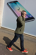 Phone user walks past Samsung shop window ad for new S6 model. Walking along the street in London's Soho, we see the man with his own handset to the ear - a call in progress. In the background is Samsung's latest smartphone model, being launched in all media this week in an attempt to win back users from a new iPhone range. Samsung Galaxy S6 and Samsung Galaxy S6 Edge are Android smartphones manufactured and marketed by Samsung Electronics. The S6 and S6 Edge jointly serve as successors to the Galaxy S5. The smartphones were officially unveiled in a press conference at Mobile World Congress on 1 March 2015.