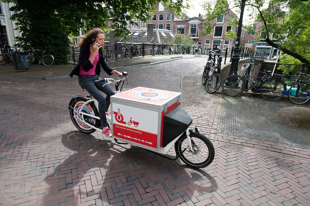 In Utrecht rijdt een vrouw al bellend op een bakfiets die te huur is bij een fietsenstalling van de gemeente.<br /> <br /> In Utrecht a woman is riding a cargo bike while on the phone.