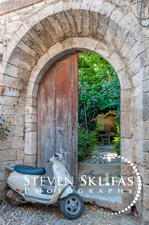 hodes. Greece. Scooter at the entrance of an old stone building with arched doorway that leads to an inner garden courtyard. The scene is typical inside the old walled town of Rhodes which is a UNESCO world heritage listed site and the best preserved, oldest and largest living medieval city in Europe.