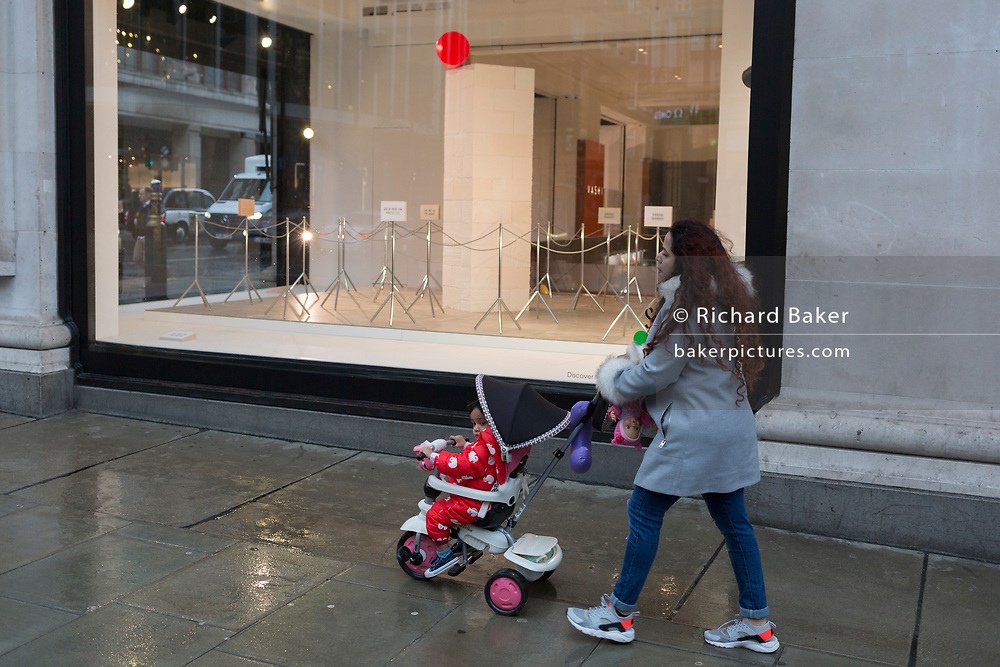 A mother walks past a window display that is part of a design theme called 'State of the Arts', at the Selfridges department store on Oxford Street, on 4th March 2019, in London England. State of the Arts is a gallery of works by nine crtically-acclaimed artists in Selfridges windows to celebrate the power of public art. Each of the artists are involved in creating a site-specific artwork at one of the new Elizabeth line stations as part of the Crossrail Art Programme.