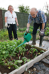 Man with learning disability with care staff watering on allotment
