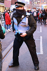 """© Licensed to London News Pictures. 20/03/2021. Manchester, UK. A police officer picks up a police radio from the road after someone pulled it from an officer's clothes and ran with it before throwing it in to the crowd. Kill the Bill """" protest in St Peter's Square and across Manchester City Centre today, in opposition to the Police, Crime, Sentencing and Courts Bill 2021 that is currently before Parliament . Photo credit: Joel Goodman/LNP"""