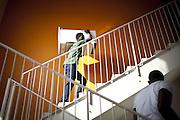 Un ragazzo trasporta un piano cottura sulle scale di una delle ex palazzine olimpiche.
