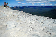 Tourists creeping to edge of graffiti-covered cliff. Blue Mountains, Katoomba, Australia