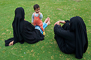 Two women and a child relaxing in the Jamia Masjid courtyard.