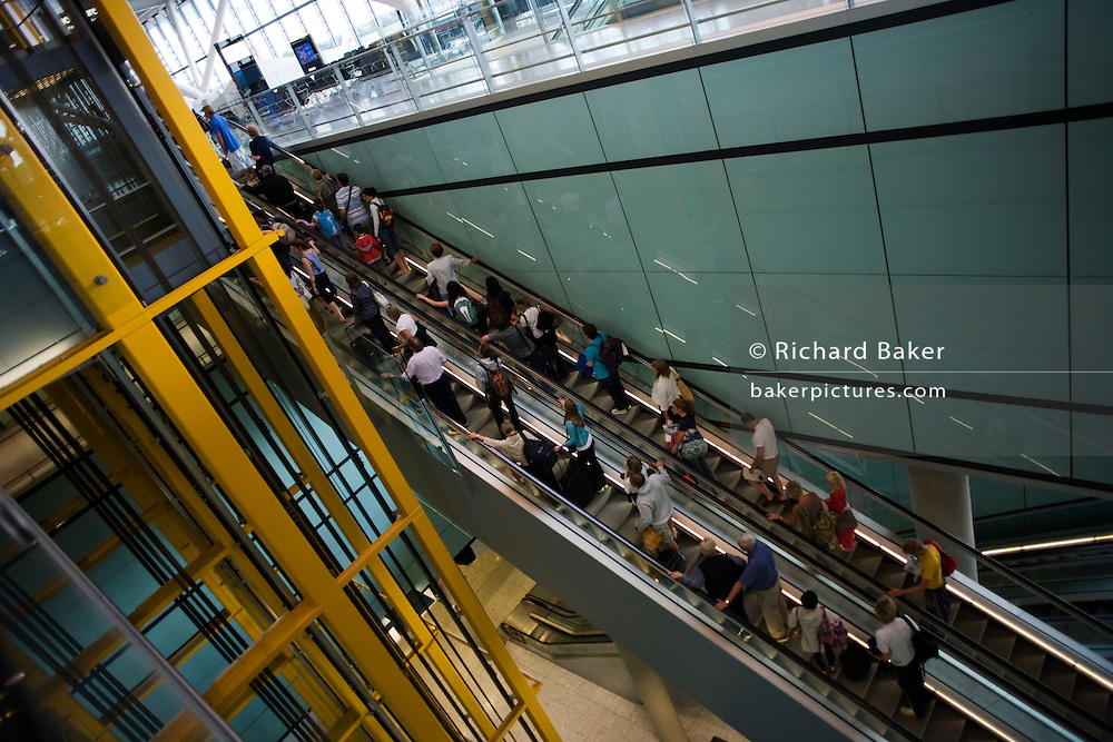 Arriving passengers on escalator and airport architecture at Heathrow's Terminal 5.