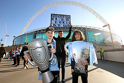 Manchester City fans hold up replicas of the Carabao Cup trophy prior to the beginning of the Carabao Cup Final at Wembley Stadium, London.