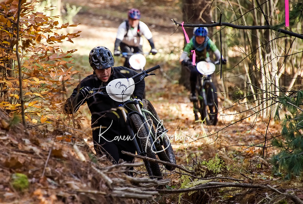 An athlete carries his bike over obstacles as he heads up Cobble Crown trail during Gunstock's Fall Flurry mountain bike race.  (Karen Bobotas Photographer)