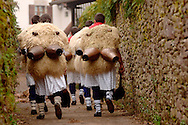 """A group of """"Joaldun"""" march carrying sheep furs and big cowbells on their backs on January 30th, 2006 at the village of Ituren, Basque Country. Joaldun groups perform an ancient traditional carnival at the villages of Ituren and Zubieta making sound their cowbells in order to wake up the earth, to ask for a good new year, a good harvest and also to keep away the bad spirits. (Ander Gillenea / Bostok Photo)"""