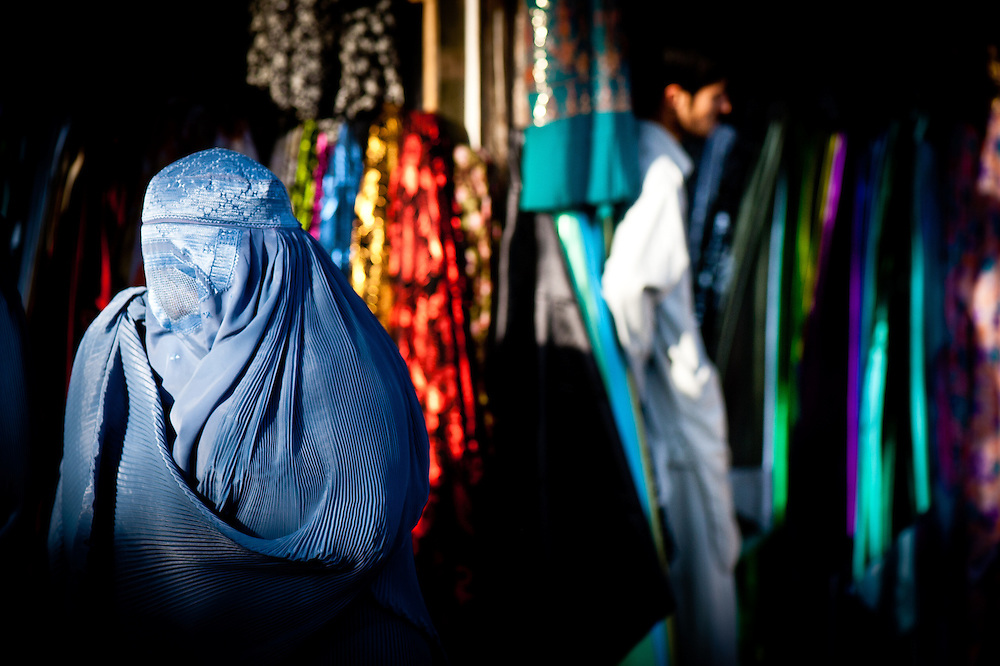 A woman walks past a stall selling fabrics in a market district of Herat.