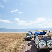 Safari vehicles stopped to watch wildelife at Ngorongoro Crater in the Ngorongoro Conservation Area, part of Tanzania's northern circuit of national parks and nature preserves.