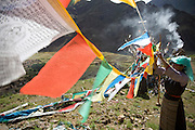 In a brisk morning breeze, two women from a nearby village tie prayer flags along a pilgrim path overlooking a reconstructed Buddhist monastery in the Tibetan Plateau. (From the book What I Eat: Around the World in 80 Diets.)  Most of the buildings remain in ruins after being destroyed in the 1960s.