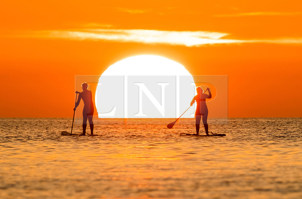 ©Licensed to London News Pictures. 19/09/2019 Aberystwyth UK. <br /> The sun setting gloriously over  Cardigan Bay silhouettes people on their paddle-boards on the sea at the end of a day of unbroken clear blue skies and warm September sunshine in Aberystwyth, west Wales.   as the 'indian summer' mini heat-wave continues over much of the souther parts of the UK. <br /> Photo credit Keith Morris/LNP