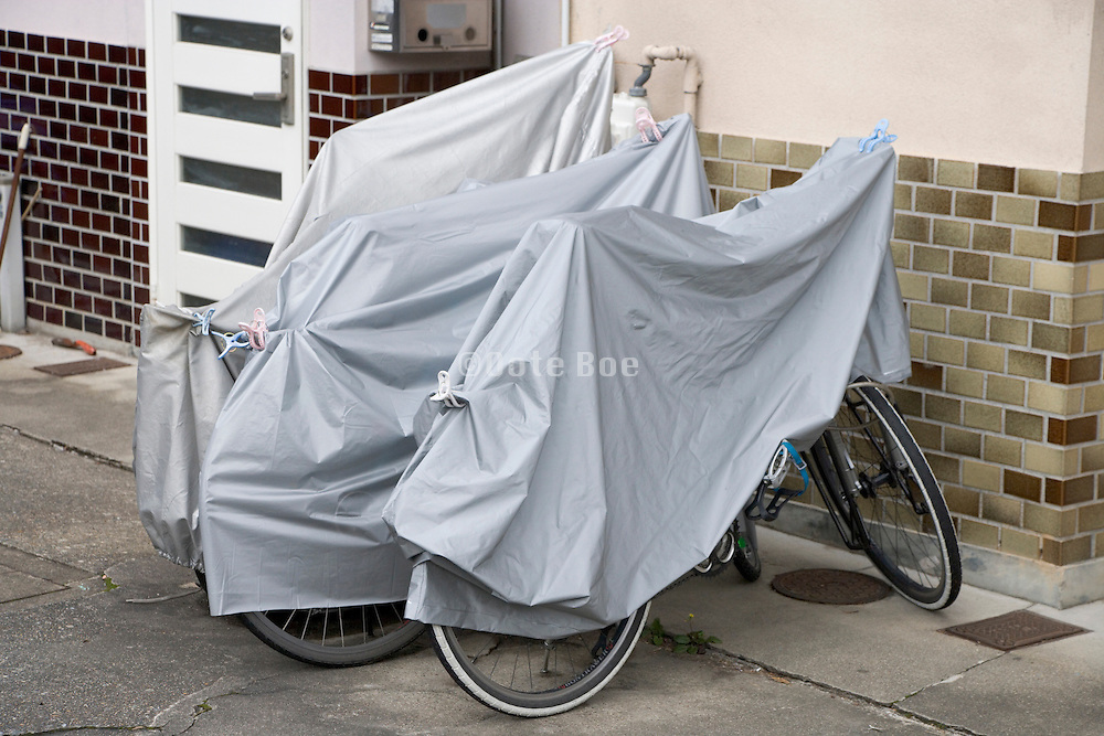 protective covered bicycles parked in front of the house Japan
