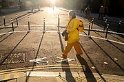 With most Londoners still working from home, a female commuter wearing yellow walks around the widened corner of Threadneedle and Old Board Streets at evening rush-hour during the third lockdown of the Coronavirus in the City of London, the capitals financial district, on 26th February 2021, in London, England.