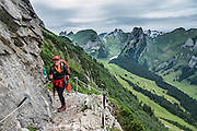 Hiking on ridge above  the lake of Fälensee in the Alpstein range, Appenzell Alps, Switzerland, Europe. Fälensee (1446 m) is in a narrow valley between Hundsteingrat and Roslen-Saxer First. Appenzell Innerrhoden is Switzerland's most traditional and smallest-population canton (second smallest by area). For licensing options, please inquire.