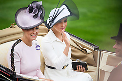© Licensed to London News Pictures. 19/06/2018. London, UK.  Meghan, Duchess of Sussex and Sophie, Countess of Wessex, arrive for Day one of Royal Ascot at Ascot racecourse in Berkshire, on June 19, 2018. The 5 day showcase event, which is one of the highlights of the racing calendar, has been held at the famous Berkshire course since 1711 and tradition is a hallmark of the meeting. Top hats and tails remain compulsory in parts of the course. Photo credit: Ben Cawthra/LNP