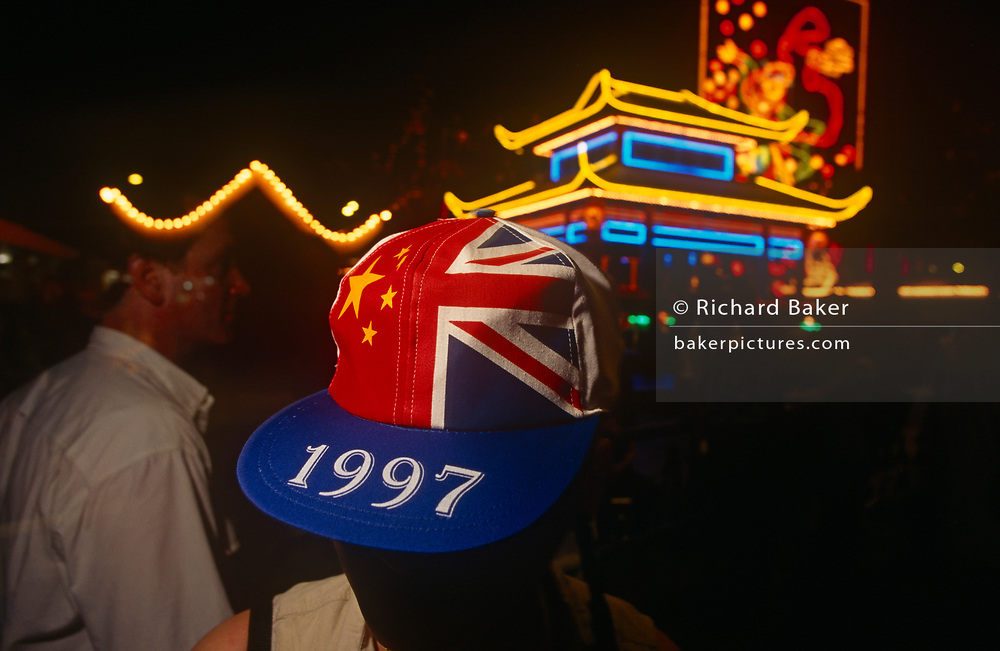 A 1997 cap is worn on the night of the Handover of sovereignty from Britain to China, on 30th June 1997, in Hong Kong, China. Midnight signified the end of British rule, and the transfer of legal and financial authority back to China. Hong Kong was once known as 'fragrant harbour' (or Heung Keung) because of the smell of transported sandal wood.