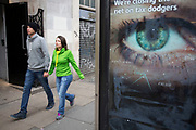 Big Brother like eye looking out from a phone box in central London. The large scale eye looks as if it is keeping surveillance on passers by. UK.