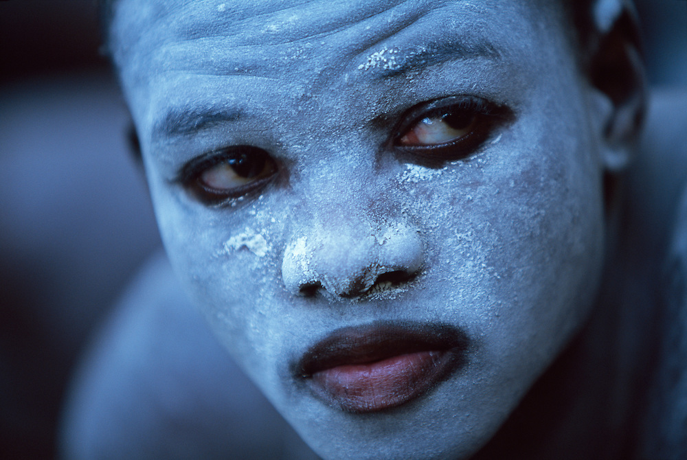 Young Xhosa initiate, who is going through the traditional Xhosa male initiation rite in Knysna, South Africa, in December 2006. He has been circumcised and is now spending a month in a special initiation camp just outside the township Khayalethu South. His face is painted with white clay to ward off attacks by witches.