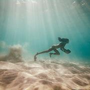 Rock running on the sandy ocean floor in clear blue water near Kailua Kona, Big Island, Hawaii.