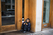 Street scene in Soho of a Asian man smoking an e-cigarette while reading from his tablet in London, England, United Kingdom.