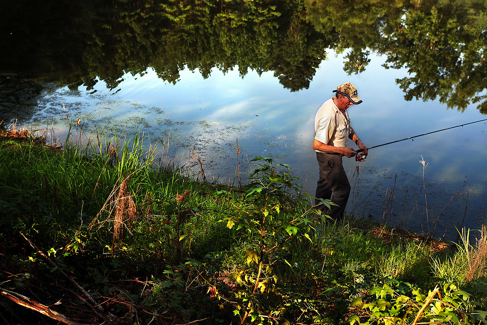 Romeo Mercado, 69, of Hidalgo, Mexico spends his day-off fishing at a pond, about a half-mile walk from the community house that he lives in at Titan Farms. Mercado, who is married and has five children, has worked at the farm for three years.