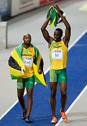 Usain Bolt (R) of Jamaica celebrates winning the gold medal and Asafa Powell of Jamaica the bronze in the men's 100 Metres Final during day two of the 12th IAAF World Athletics Championships at the Olympic Stadium on August 16, 2009 in Berlin, Germany. Bolt set a new World Record of 9.58. (Photo by Vid Ponikvar / Sportida)