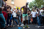 A man striped naked to his waist dances to a bongo drum band in Portobello Road. The Notting Hill Carnival has been running since 1966 and is every year attended by up to a million people. The carnival is a mix of amazing dance parades and street parties with a distinct Caribbean feel.