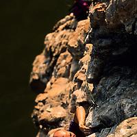Jose Pereyra climbs an unnamed 5.10 with partner Will Hair high above the Nam Ou River, Ban Pak Ou, Luang Phrabang, Laos