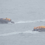 Zodiacs full of Seabourn guests pass each other in the waters of Half Moon Island, Antarctica.