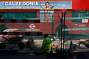 London bus with side advert for Italian swimwear label Calzedonia, stopped at lights by construction work in central London. Green netting separates roadworks on Regents Street, from passing traffic - the common cause of vehicle delays and disruption in the capital that leads to frustration from those behind the wheel and loss of business. A workman stands in a hole and above him is a beautiful woman modelling swimwear for the Calzedonia brand.