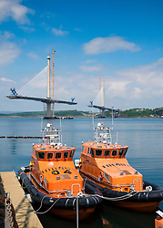 New Queensferry crossing bridge under construction crossing the River Forth and modern lifeboats at South Queensferry in Scotland United Kingdom.