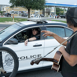 Musician and handyman Douglas Crawford greets an Austin police officer as he strums his guitar for spare change near his camp at the corner of Ben White Blvd. and south Congress Avenue in Austin, TX where he's lived for over a year. Crawford, 60, says he stays to himself and isn't worried about Austin's new homeless crackdown and camping ban starting Tuesday.