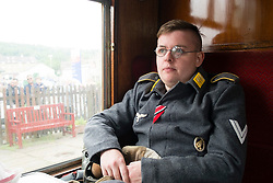 A reenactor potraying a German Paratrooper (Fallschirmjäger) in walking out uniform travels on a train during the East Lancashire Railway 1940's Weekend. He wears the rank of Obergefreiter on his left sleeve. The medal ribbons for the Iron Cross second class (EK2) and Eastern Front Medal (Ostmedaille) on the front of his fight jacket (Fliegerbluse) and the Paratrooper badge (Fallschirmspringerabzeichen) on the left front. <br /> <br />  Copyright Paul David Drabble<br />  www.pauldaviddrabble.co.uk