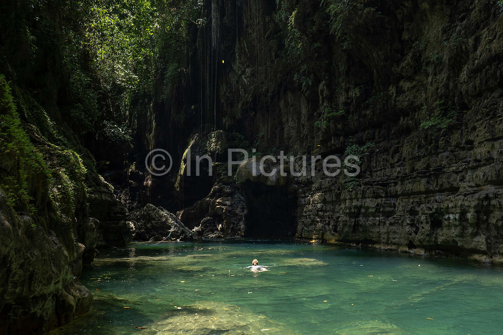 A Euopean woman swimming at the Green Canyon near Pangandaran on the 30th October 2019 in Java in Indonesia.